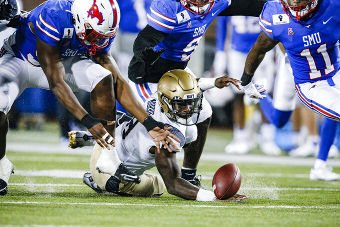 Navy quarterback Dalen Morris (8) fumbles the ball during the first half of the team's NCAA college football game against SMU on Saturday, Oct. 31, 2020, in Dallas. SMU defensive end Gary Wiley, left, recovered the ball. (AP Photo/Brandon Wade)