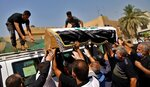 Mourners load the flag-draped coffin of Hisham al-Hashimi during his funeral, in the Zeyouneh area of Baghdad, Iraq, Tuesday, July, 7, 2020. Al-Hashimi, an Iraqi analyst who was a leading expert on the Islamic State and other armed groups was shot dead in Baghdad on Monday. (AP Photo/Khalid Mohammed)