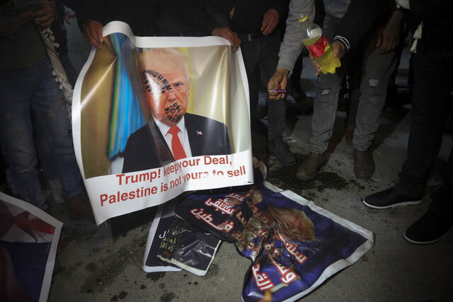 Palestinian hold a poster showing U.S. President Donald Trump as they protest the American peace plan in Bethlehem, Monday, Jan. 27, 2020. Israeli Prime Minister Benjamin Netanyahu arrived in Washington Sunday night vowing to