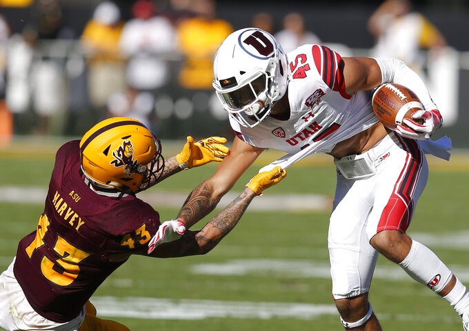 Arizona State safety Jalen Harvey (43) holds on for a tackle of Utah wide receiver Samson Nacua in the first half during an NCAA college football game, Saturday, Nov. 3, 2018, in Tempe, Ariz. (AP Photo/Rick Scuteri)