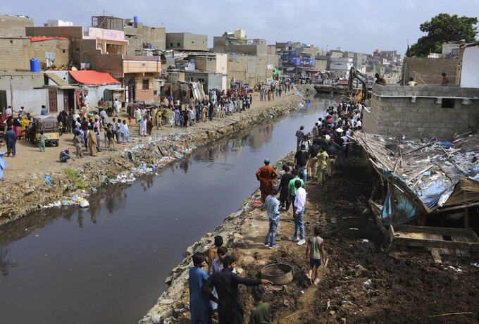 Residents watch the arrival of local authorities to demolish illegal construction alongside a drainage canal which saw flooding last week due to heavy monsoon rains, in Karachi, Pakistan, Wednesday, Sept. 2, 2020. Flash floods triggered by heavy rains killed some people and damaged scores of houses in Pakistan's scenic northwestern Swat Valley, a spokesman said Wednesday, as rescuers assisted residents in the port city of Karachi where last week's rains wreaked havoc that killed dozens. (AP Photo/Fareed Khan)