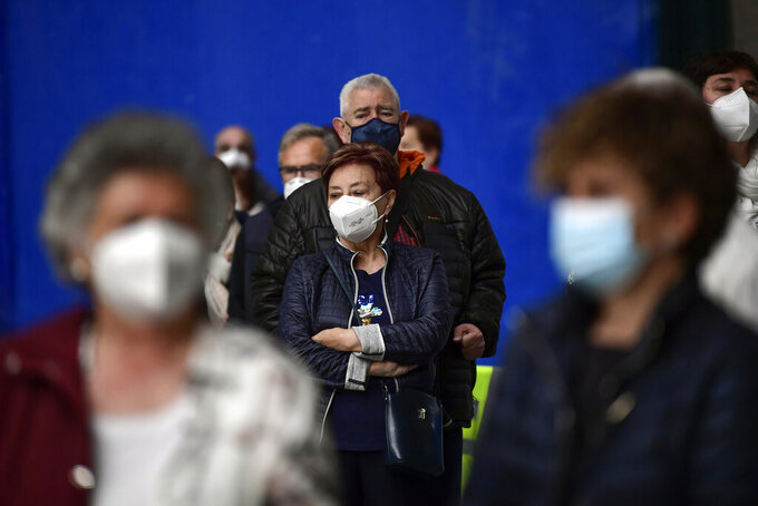 People wearing face mask protection to prevent the spread of the coronavirus while waiting to receive a shot of Pfizer vaccine during a COVID-19 vaccination campaign, in Pamplona, northern Spain, Friday, May 7, 2021.(AP Photo/Alvaro Barrientos)