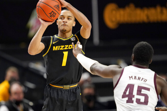 Missouri guard Xavier Pinson (1) shoots a 3-point basket as Texas A&M forward Kevin Marfo (45) tries to defend during the first half of an NCAA college basketball game Saturday, Jan. 16, 2021, in College Station, Texas. (AP Photo/Sam Craft)