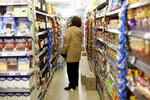 A woman checks prices at a supermarket in Buenos Aires, Argentina, Wednesday, Aug. 14, 2019. President Mauricio Macri announced economic relief for poor and working-class Argentines that include an increased minimum wage, reduced payroll taxes, a bonus for informal workers and a freeze in gasoline prices. The conservative leader said Wednesday he's acting in recognition of the