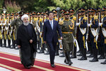 Japanese Prime Minister Shinzo Abe, center, reviews an honor guard as he is welcomed by Iranian President Hassan Rouhani, left, in an official arrival ceremony at the Saadabad Palace in Tehran, Iran, Wednesday, June 12, 2019. The Japanese leader is in Tehran on an mission to calm tensions between the U.S. and Iran. (AP Photo/Ebrahim Noroozi)