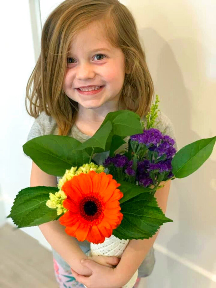 This Feb. 14, 2019 photo provided by her uncle David Smith shows 6-year-old Aria Hill posing with flowers near Eagle Mountain in northern Utah during a family trip. Relatives say the 6-year-old Utah girl who died after her father accidentally struck her with a golf ball was a loving, playful child. Smith described her as a happy child who greeted strangers and enjoyed spending time with her parents, while speaking to reporters on Wednesday, July 17. Police say the ball struck Hill Monday morning, July 15, while the father and daughter were golfing at Sleepy Ridge Golf Course in Orem. (David Smith via AP)