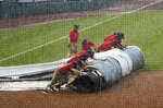Grounds crew members unroll the tarp to cover the baseball diamond from a heavy downpour delaying a baseball game during the sixth inning between the Washington Nationals and the Baltimore Orioles in Washington, Sunday, Aug. 9, 2020. (AP Photo/Manuel Balce Ceneta)