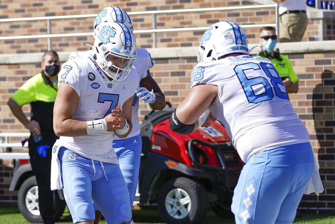 North Carolina quarterback Sam Howell (7) celebrates a touchdown with lineman Brian Anderson (68) during the first half of an NCAA college football game against Duke at Wallace Wade Stadium, Saturday, Nov. 7, 2020, in Durham, N.C. (Jim Dedmon/Pool Photo via AP)