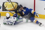 Vancouver Canucks' Quinn Hughes (43) and St. Louis Blues' Zach Sanford (12) battle for the puck during the second period in Game 1 of an NHL hockey Stanley Cup first-round playoff series, Wednesday, Aug. 12, 2020, in Edmonton, Alberta. (Jason Franson/The Canadian Press via AP)