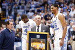 North Carolina coach Roy Williams is presented with a photograph of himself with Dean Smith by players Brandon Robinson and Garrison Brooks following an NCAA college basketball game in Chapel Hill, N.C., Monday, Dec. 30, 2019. Williams tied Dean Smith with 879 careers wins. Scott Smith, son of the late Dean Smith, is seen at left. (AP Photo/Gerry Broome)