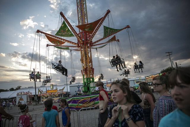 People wait to ride a revolving swing at the Perry State Fair in New Lexington, Ohio, Friday, July 24, 2020. In the towns that speckle the Appalachian foothills of southeast Ohio, the pandemic has barely been felt. Coronavirus deaths and racial protests _ events that have defined 2020 nationwide _ are mostly just images on TV from a distant America. (AP Photo/Wong Maye-E)