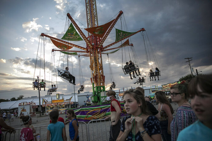 People wait to ride a revolving swing at the Perry State Fair in New Lexington, Ohio, Friday, July 24, 2020. In the towns that speckle the Appalachian foothills of southeast Ohio, the pandemic has barely been felt. Coronavirus deaths and racial protests - events that have defined 2020 nationwide - are mostly just images on TV from a distant America. (AP Photo/Wong Maye-E)