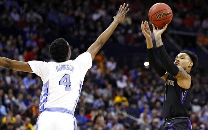 Washington's David Crisp (1) shoots against North Carolina's Brandon Robinson (4) in the first half during a second round men's college basketball game in the NCAA Tournament in Columbus, Ohio, Sunday, March 24, 2019. (AP Photo/John Minchillo)