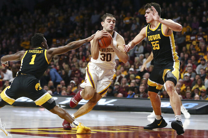 Minnesota's Alihan Demir handles the ball through the defense of Iowa's Joe Toussaint (1) and Luka Garza (55) during an NCAA college basketball game Sunday, Feb. 16, 2020, in Minneapolis. (AP Photo/Stacy Bengs)