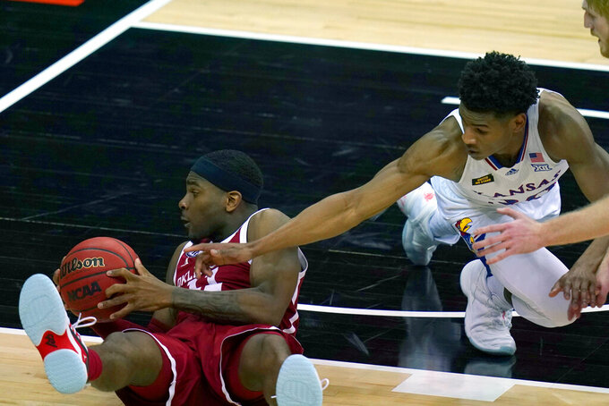 Oklahoma guard De'Vion Harmon (11) hits the floor while covered by Kansas guard Ochai Agbaji (30) during the second half of an NCAA college basketball game in the quarterfinal round of the Big 12 men's tournament in Kansas City, Mo., Thursday, March 11, 2021. Kansas defeated Oklahoma 69-62. (AP Photo/Orlin Wagner)