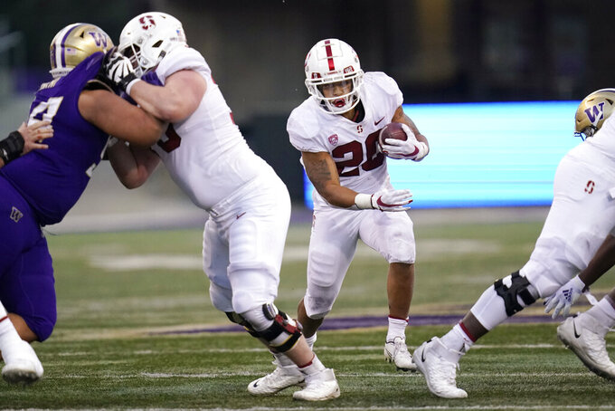 Stanford running back Austin Jones, right, eyes a hole on a carry against Washington in the second half of an NCAA college football game Saturday, Dec. 5, 2020, in Seattle. (AP Photo/Elaine Thompson)