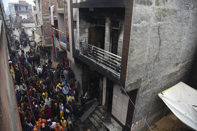 People gather around a warehouse where a fire broke out in the early hours of Monday at Kirari area of New Delhi, India, Monday, Dec.23, 2019. The blaze killed 9 people and left at least 3 injured, a fire official said. (AP Photo)