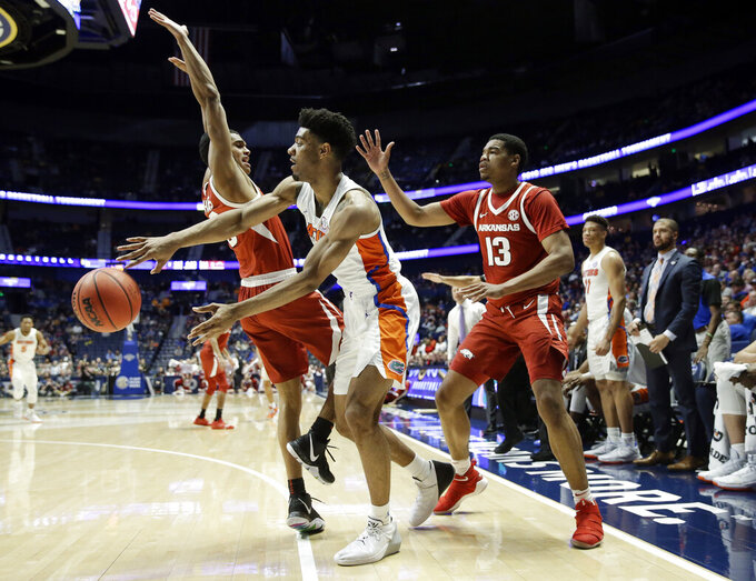 Florida's Jalen Hudson, center, passes away from Arkansas defenders Jalen Harris, left, and Mason Jones (13) in the second half of an NCAA college basketball game at the Southeastern Conference tournament Thursday, March 14, 2019, in Nashville, Tenn. Florida won 66-50. (AP Photo/Mark Humphrey)
