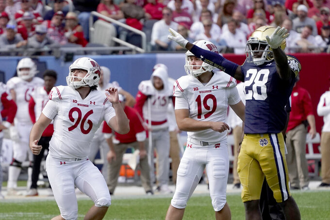 Notre Dame cornerback TaRiq Bracy signals a missed field goal by Wisconsin place kicker Collin Larsh (19) as holder Conor Schlichting watches during the second half of an NCAA college football game Saturday, Sept. 25, 2021, in Chicago. Notre Dame won 41-13. (AP Photo/Charles Rex Arbogast)