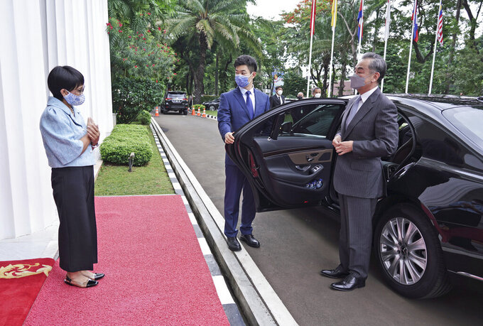 In this photo released by Indonesian Foreign Ministry, Indonesian Foreign Minister Retno Maraud, left, greets her Chinese counterpart Wang Yi upon his arrival for their meeting in Jakarta, Indonesia, Wednesday, Jan. 13, 2021. Wang pledged that China will help Indonesia defeat the coronavirus, including providing vaccines and the strengthen economic cooperation with Indonesia in addition to strengthening cooperation in the health sector in overcoming the COVID-19 pandemic. (Indonesian Foreign Ministry via AP)