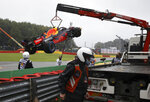 The car of Red Bull driver Sergio Perez of Mexico is lifted onto a flatbed after he crashed on his way to the grid during the Formula One Grand Prix at the Spa-Francorchamps racetrack in Spa, Belgium, Sunday, Aug. 29, 2021. (AP Photo/Olivier Matthys)