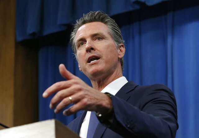 FILE - In this July 23, 2019, file photo, Gov. Gavin Newsom talks to reporters at his Capitol office in Sacramento, Calif. California will attempt to use its massive market power to increase the availability and lower the cost of prescription drugs. The new law that Newsom approved Monday, Sept. 28, 2020, requires the California Health and Human Services Agency to create partnerships designed to increase competition, lower prices and reduce shortages for generic prescription drugs. (AP Photo/Rich Pedroncelli, File)
