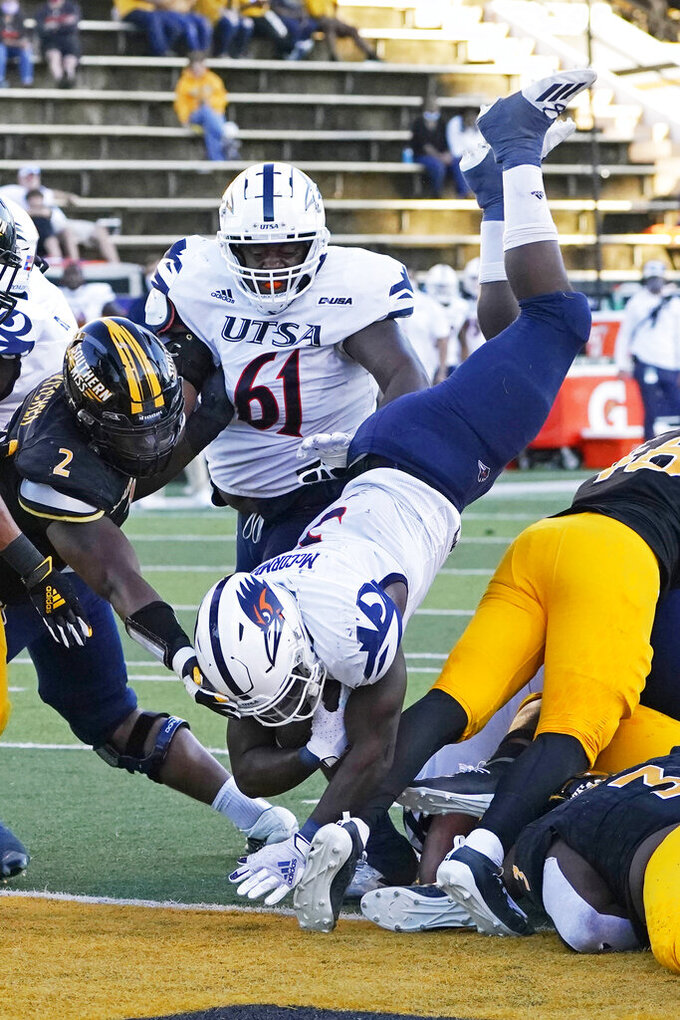 UTSA running back Sincere McCormick (3) dives over Southern Mississippi linebacker Averie Habas (46) for a short yardage touchdown during the second half of an NCAA college football game, Saturday, Nov. 21, 2020, in Hattiesburg, Miss. UTSA won 23-20. (AP Photo/Rogelio V. Solis)