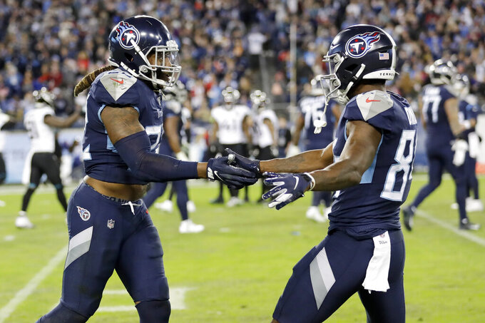 Tennessee Titans running back Derrick Henry (22) is congratulated by wide receiver Corey Davis, right, after Henry scored a touchdown against the Jacksonville Jaguars in the second half of an NFL football game Sunday, Nov. 24, 2019, in Nashville, Tenn. (AP Photo/James Kenney)