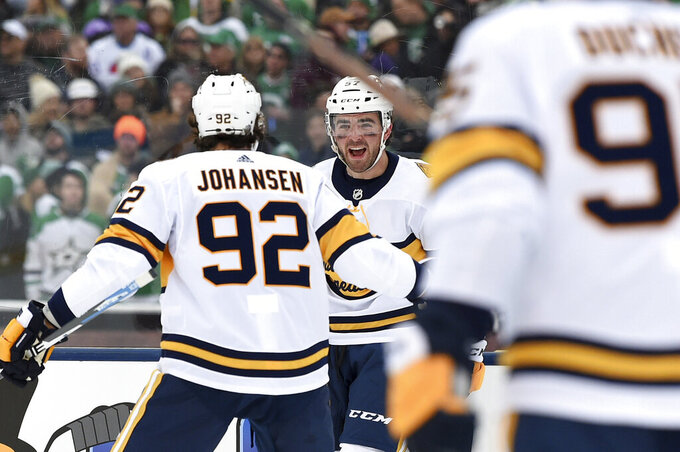 Nashville Predators defenseman Dante Fabbro, center, celebrates with center Ryan Johansen (92) after scoring a goal in the first period of the NHL Winter Classic hockey game at the Cotton Bowl, Wednesday, Jan. 1, 2020, in Dallas. (AP Photo/Jeffrey McWhorter)