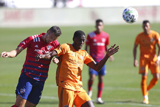 Matt Hedges, left, of FC Dallas and Wilfried Zahibo, right, of Houston Dynamo head the ball during an MLS soccer match, Saturday, Oct. 31, 2020, in Frisco, Texas. (Omar Vega/The Dallas Morning News via AP)