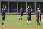 Atlanta Braves' Ronald Acuña Jr., center, stretches with teammates during team practice at Truist Park on Sunday, July 5, 2020, in Atlanta. (AP Photo/Brynn Anderson)