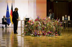 From left, German President Frank-Walter Steinmeier, German Chancellor Angela Merkel and relatives of victims of the Corona pandemic attend a memorial service in Berlin, Germany, Sunday, April 18, 2021 in remembrance of Germany's corona dead. (AP Photo/Michael Sohn, pool)
