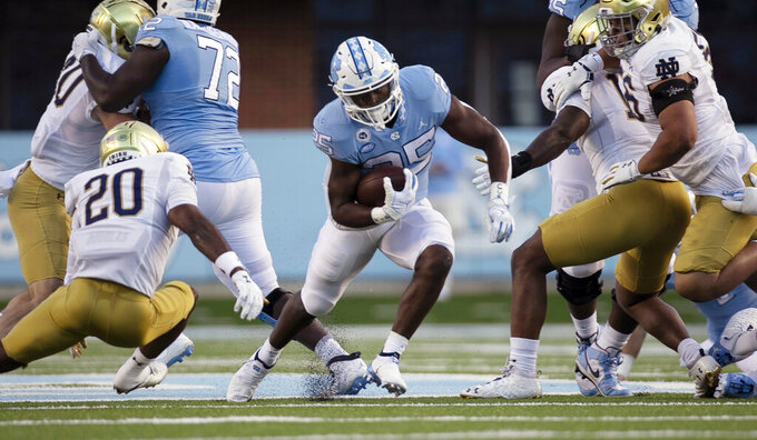 North Carolina's Javonte Williams (25) breaks away from Notre Dame's Shaun Crawford (20) in the first quarter of an NCAA college football game, Friday, Nov. 27, 2020, at Kenan Stadium in Chapel Hill, N.C. (Robert Willett/The News & Observer via AP)