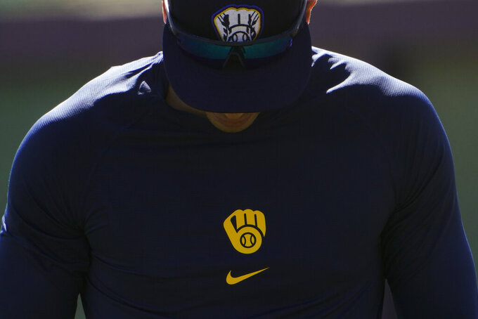 Milwaukee Brewers' Christian Yelich walks past a batting cage during the team's spring training baseball workout in Phoenix, Tuesday, Feb. 23, 2021. (AP Photo/Jae C. Hong)