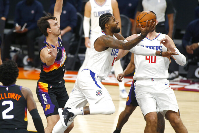 Los Angeles Clippers forward Paul George, center, drives to the basket past the defense of Phoenix Suns' Dario Saric, left, during the first half of an NBA basketball game Sunday, Jan. 3, 2021, in Phoenix. (AP Photo/Ralph Freso)