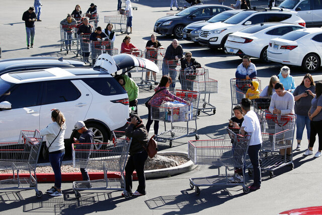 A line of people waiting to buy supplies amid coronavirus fears snakes through a parking lot at a Costco, Saturday, March 14, 2020, in Las Vegas. For most people, the new coronavirus causes only mild or moderate symptoms. For some it can cause more severe illness, especially in older adults and people with existing health problems. (AP Photo/John Locher)