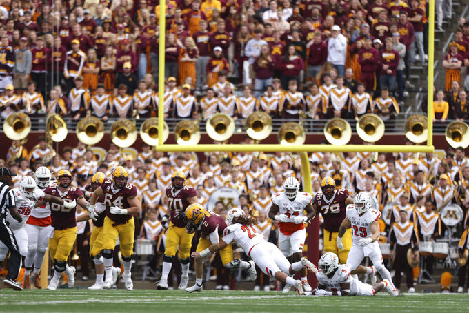 Minnesota quarterback Tanner Morgan (2) is tackled by Bowling Green linebacker Diego Neri (24) during an NCAA college football game Saturday, Sept. 25, 2021, in Minneapolis. Bowling Green won 14-10. (AP Photo/Stacy Bengs)