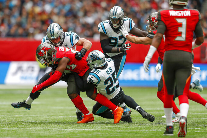 Tampa Bay Buccaneers running back Peyton Barber (25) is tackled by Carolina Panthers strong safety Eric Reid (25) and linebacker Devante Bond (59) during the first quarter of an NFL football game, Sunday, Oct. 13, 2019, at Tottenham Hotspur Stadium in London. (AP Photo/Alastair Grant)