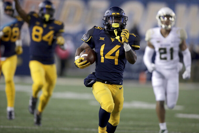 West Virginia running back Tevin Bush (14) runs for a touchdown during the first half of an NCAA college football game against Baylor, Thursday, Oct. 25, 2018, in Morgantown, W.Va. (AP Photo/Raymond Thompson)
