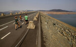 FILE - In this Aug. 22, 2021, file photo, pedestrians walk across Oroville Dam at Lake Oroville State Recreation Area as drought conditions continue in Butte County, Calif. Californians failed to significantly cut back their water consumption in July, state officials announced Tuesday, Sept. 21, 2021, foreshadowing some difficult decisions for Gov. Gavin Newsom's administration as an historic drought lingers into the fall. (AP Photo/Ethan Swope, File)
