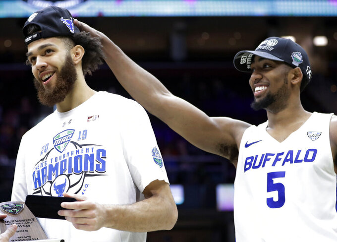 Buffalo's CJ Massinburg, right, pulls on Jeremy Harris's cap after Buffalo defeated Bowling Green 87-73 in an NCAA college basketball game for the Mid-American Conference men's tournament title Saturday, March 16, 2019, in Cleveland. (AP Photo/Tony Dejak)