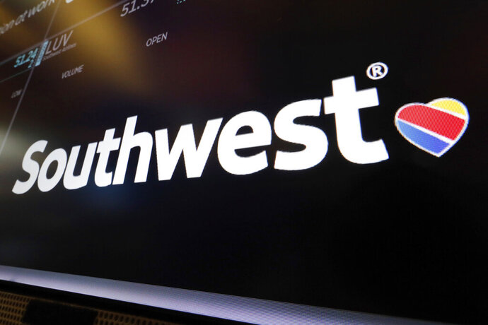 """FILE - In this Monday, March 18, 2019, file photo, the logo for Southwest Airlines appears above a trading post on the floor of the New York Stock Exchange. Passengers on a Southwest Airlines flight got more than a bag of nuts when they boarded their plane. They received a Nintendo Switch system and a download code for the digital version of the """"Super Mario Maker 2"""" game to enjoy as Flight 2246 traveled from Dallas to San Diego on Wednesday, July 17, 2019. Many of the passengers were headed to Comic Con in the California city.  (AP Photo/Richard Drew, File)"""