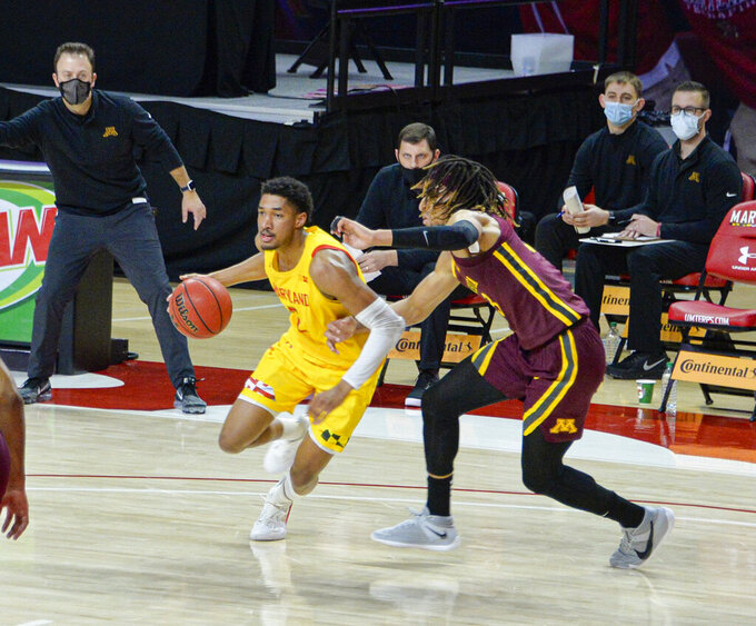Maryland guard Aaron Wiggins, left, drives the floor against Minnesota during the first half of an NCAA college basketball game, Sunday, Feb. 14, 2021, in College Park, Md. (Kevin Richardson/The Baltimore Sun via AP)