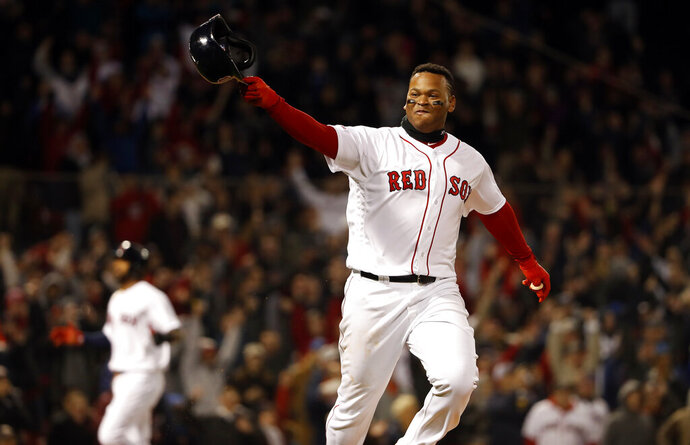 Boston Red Sox's Rafael Devers points to the team's dugout after hitting a walk-off single against the Toronto Blue Jays during the ninth inning of a baseball game Thursday, April 11, 2019, at Fenway Park in Boston. Boston won 7-6. (AP Photo/Winslow Townson)