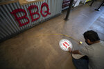 Francisco Ocampo installs a sign on the floor alerting social distancing measures at the Liberty Public Market restaurant Thursday, May 21, 2020, in San Diego. San Diego County began to relax rules regarding social distancing and efforts to slow the spread of the new coronavirus Thursday, as restaurant workers scrambled to prepare for limited indoor dining. (AP Photo/Gregory Bull)