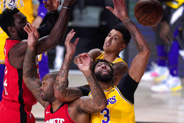 Los Angeles Lakers' Anthony Davis (3) and P.J. Tucker, left, reach for the ball during the first half of an NBA conference semifinal playoff basketball game Thursday, Sept. 10, 2020, in Lake Buena Vista, Fla. (AP Photo/Mark J. Terrill)