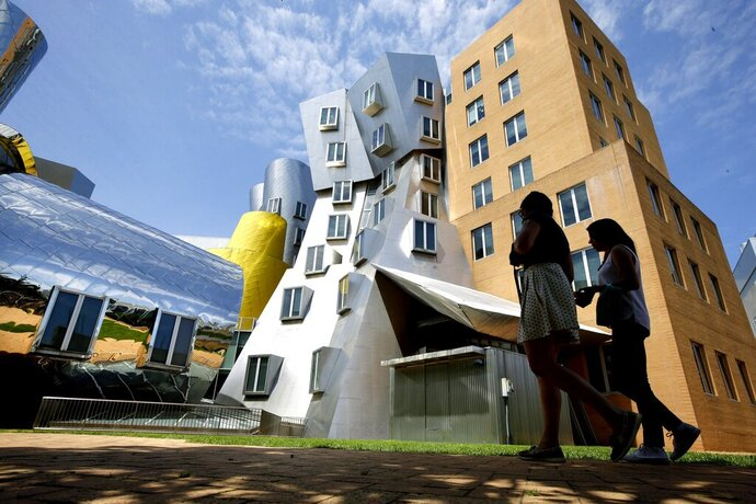 FILE - In this July 16, 2019, file photo people walk past the Ray and Maria Stata Center building on the campus of Massachusetts Institute of Technology, in Cambridge, Mass. MIT has agreed to provide captions for more of its publicly available online videos as part of a settlement announced Tuesday, Feb. 18, 2020, of a lawsuit filed by the National Association of the Deaf, which said the school was discriminating against people with hearing disabilities by not adequately or accurately captioning videos of lectures and other programs it posts online. (AP Photo/Steven Senne, File)