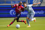 FC Dallas forward Fafa Picault (9) and Sporting Kansas City defender Luis Martins (36) chase the ball during the first half of an MLS soccer match in Kansas City, Kan., Saturday, Sept. 19, 2020. (AP Photo/Orlin Wagner)