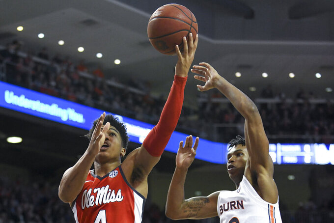 Mississippi guard Breein Tyree (4) shoots next to Auburn guard Allen Flanigan (22) during the first half of an NCAA college basketball game Tuesday, Feb. 25, 2020, in Auburn, Ala. (AP Photo/Julie Bennett)