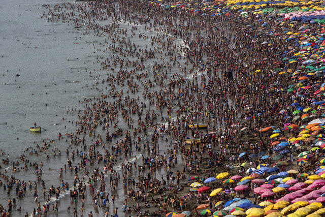 This Feb. 16, 2020 photo shows the the Agua Dulce public beach packed with thousands of beachgoers in Lima, Peru. On some weekends during the Southern Hemisphere summer, which runs from December until March, as many as 40,000 people a day visit the half-mile-long (kilometer-long) strip of Agua Dulce. (AP Photo/Rodrigo Abd)